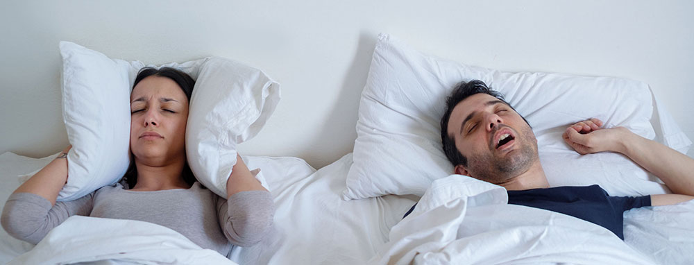 couple sleeping in bed, husband snoring